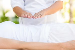 Example of a Reiki healing, the practitioners hands suspended above the patient.