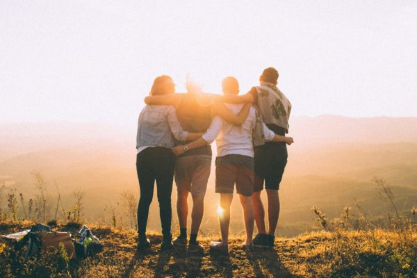 friends together at sunrise overlook in nature